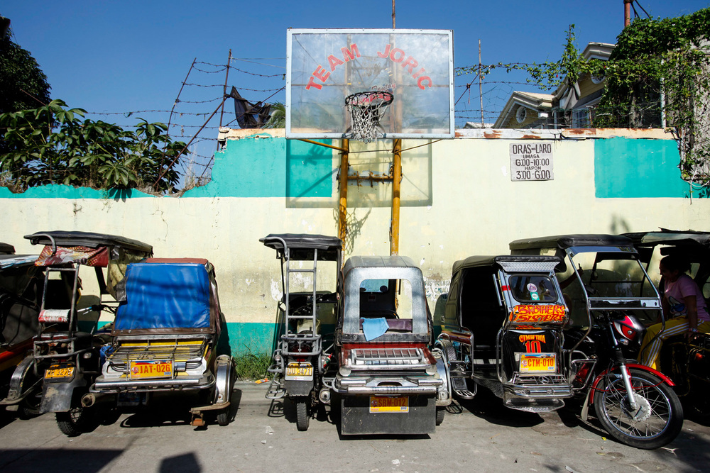 A basketball court by an alley that also serves as a dock for tricycles waiting for passengers during the day in Rizal, Philippines.
