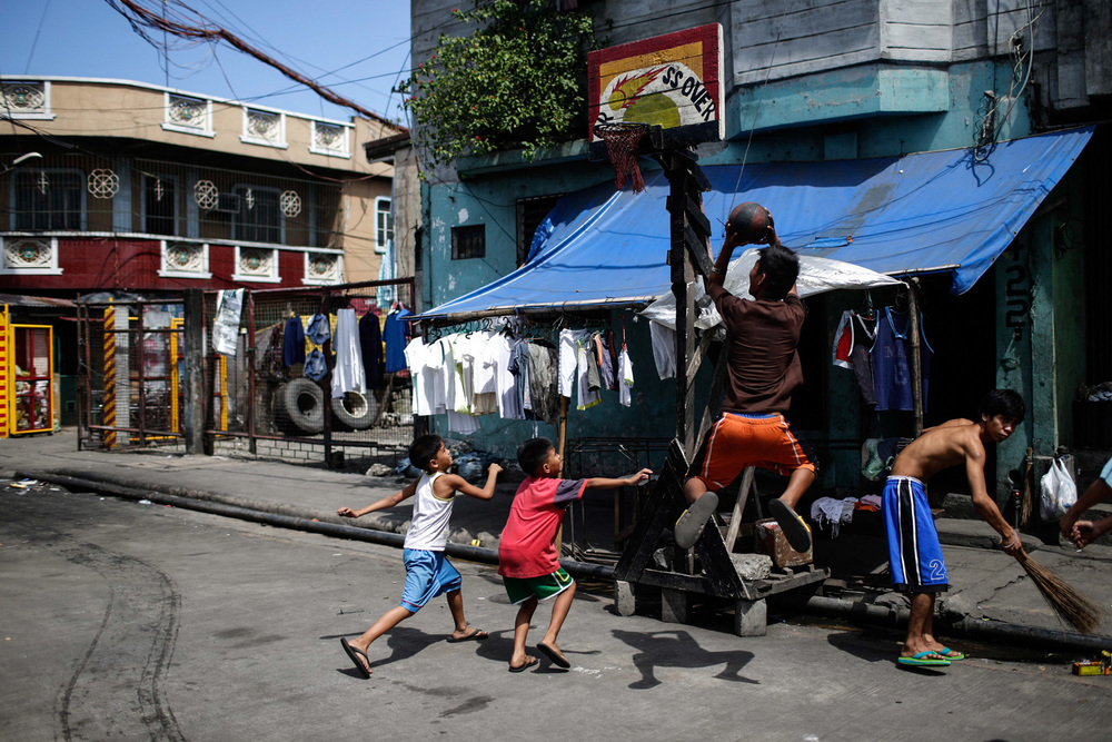 Children play at a makeshift basketball court in the slum are of Tondo, one of the most densely populated areas of Metro Manila, Philippines.
