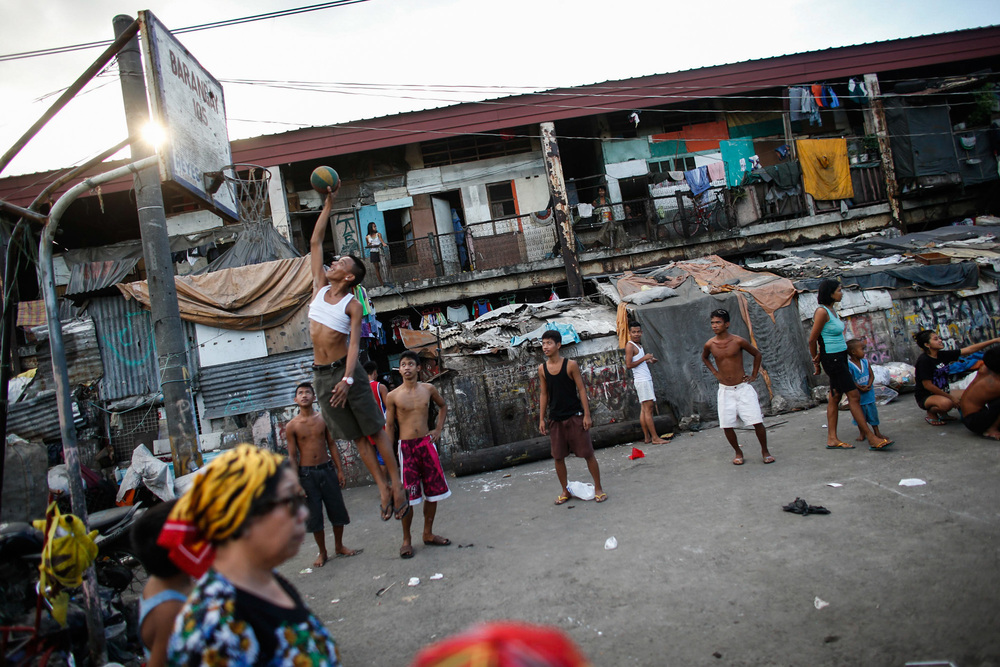 Residents play a game of basketball in a slum area in Tondo, Metro Manila