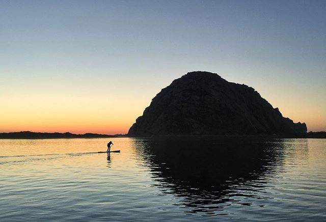 A person paddles by Morro Rock at Morro Bay, California. #MorroBay #California #Travel #iPhone #MorroBayRock #Sunset #EverydayCalifornia