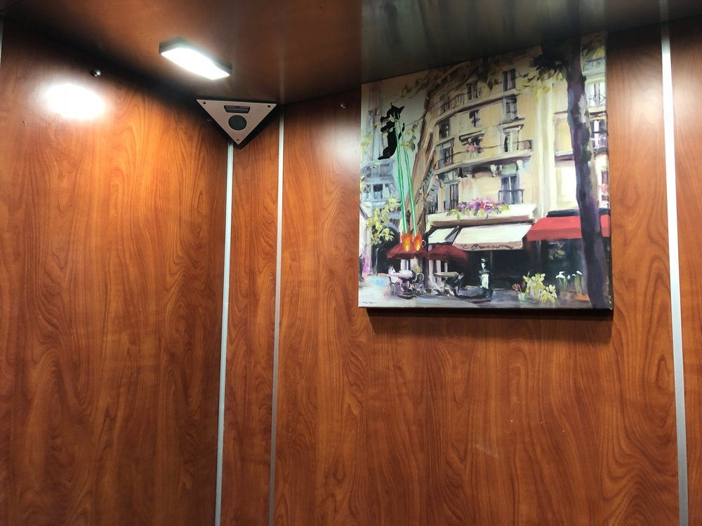 The quiet, Parisian café scene makes a triumphant return to our elevator.