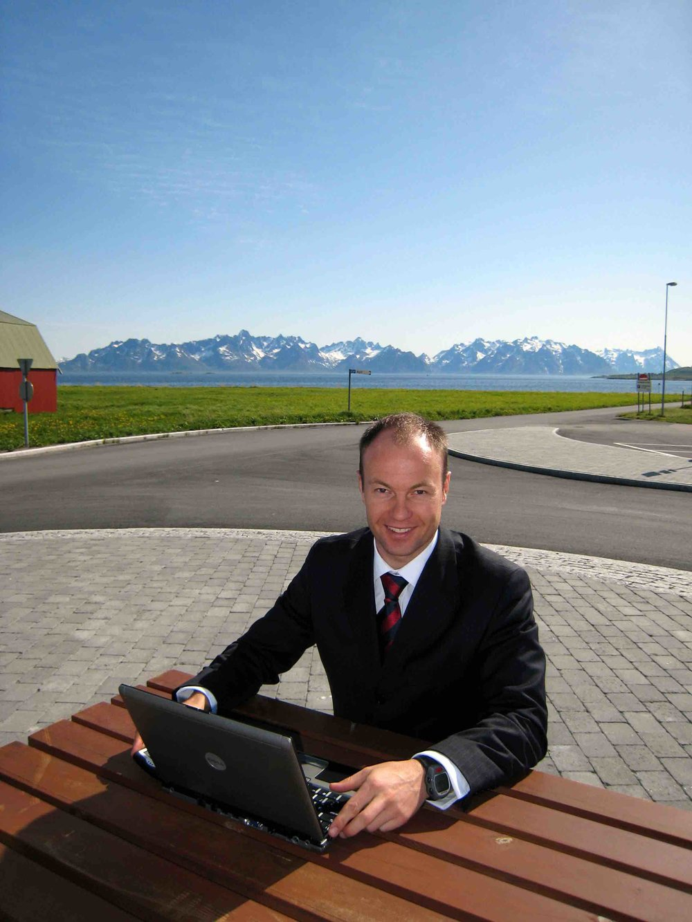 Founder - Keith, back when he had a little more hair and worked in Norway. Yes that's an unfashionable Polar watch on the left arm and a Blackberry in the right hand. This was the scene after the opening of the first Boots Chemist in the Arctic Circle. That's the Lofoten Wall in the background. Norway is beautiful, you should visit. Back then Blackberrys had 5 DAYS battery life.