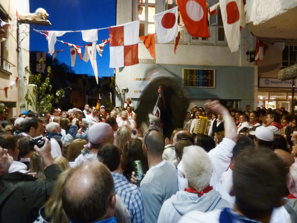 Outside the 'Golden Lion' pub, home of the Oss. The Oss - the blurred black shape - tilts and whirls in a last frenzied dance while the people of Padstow bellow out the final renditions of the MayDay Song, with tears visibly welling in their eyes, as they watch the Oss finally be put to sleep for another year.