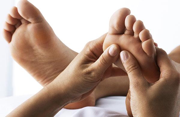 therapist_giving_a_reflexology_massage_on_the_bottom_of_a_foot_jpg-600x390.jpeg