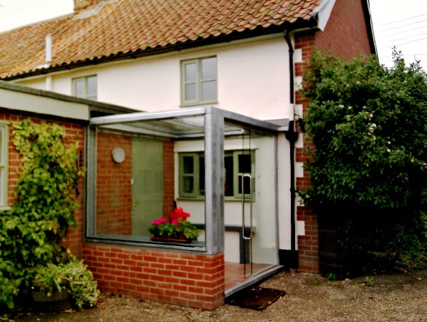 The porch has a brick plinth/seat with the main structure in galvanised steel. A high proportion of glass allows plenty of daylight in through the kitchen window and maintains views down the garden.