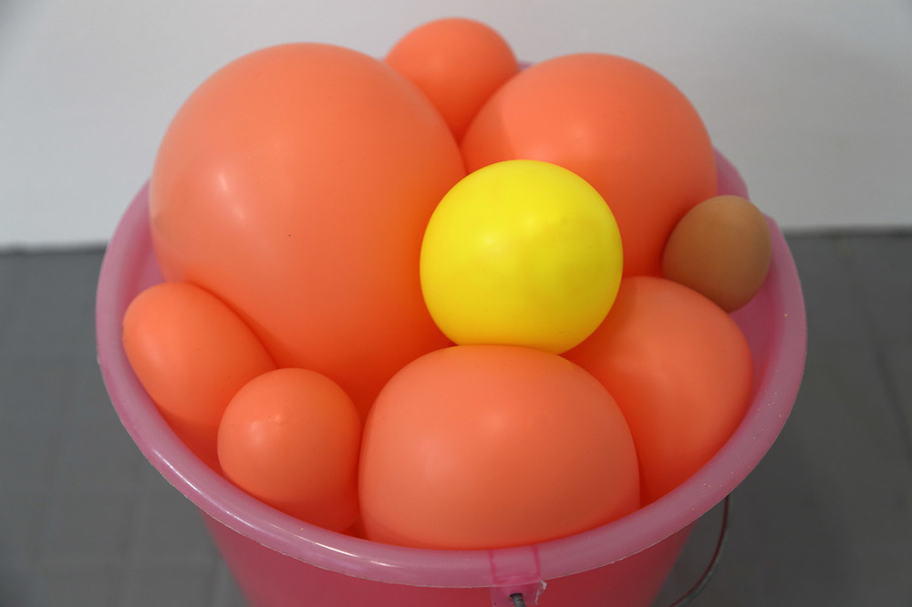 Materials: plastic bucket with metal handle, latex balloons, egg shaped rubber bouncy ball, sound (hidden mp3 player, looped, hidden mini speaker)