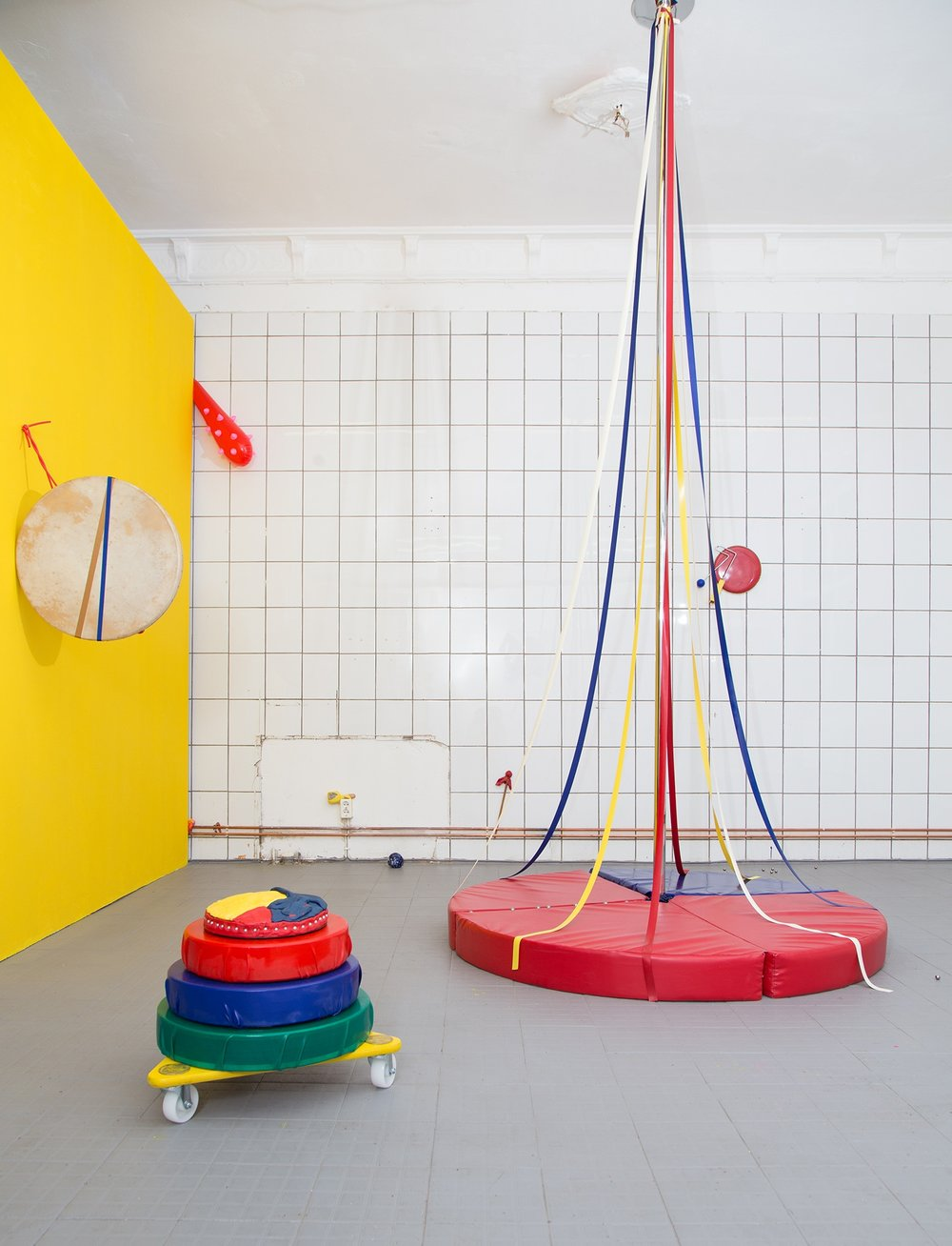 Four on the Floor (Work Work Work Work)    Installation view at HPFA Berlin:  Materials (not including mobile sculpture): Vinyl crash mat, pole dancing pole, latex ribbons and rope, liquid and sheet material latex, ball bearings, ceramics, felt and wooden shakers and beaters, vinyl blow up toy, hand drum, gouache and acrylic paint, glitter nail polish, tape, satin ribbons, vanilla cake, yellow food colouring, silver sugar pearls, fondant, yellow wall.  Dimensions: height shown - 3.5 metres, width variable