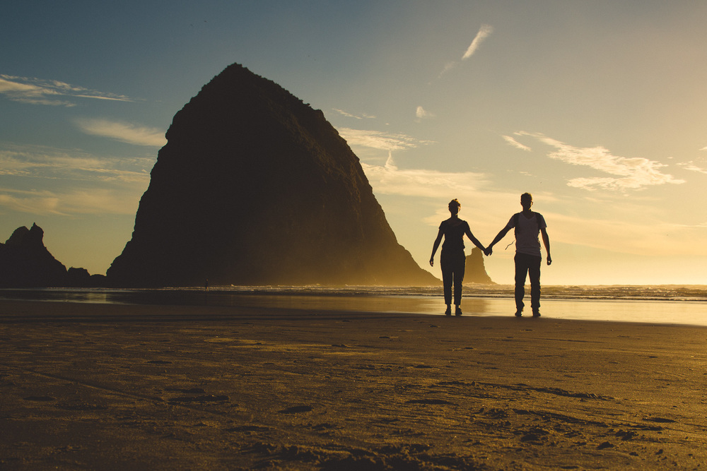Couple-holding-hands-cannon-beach