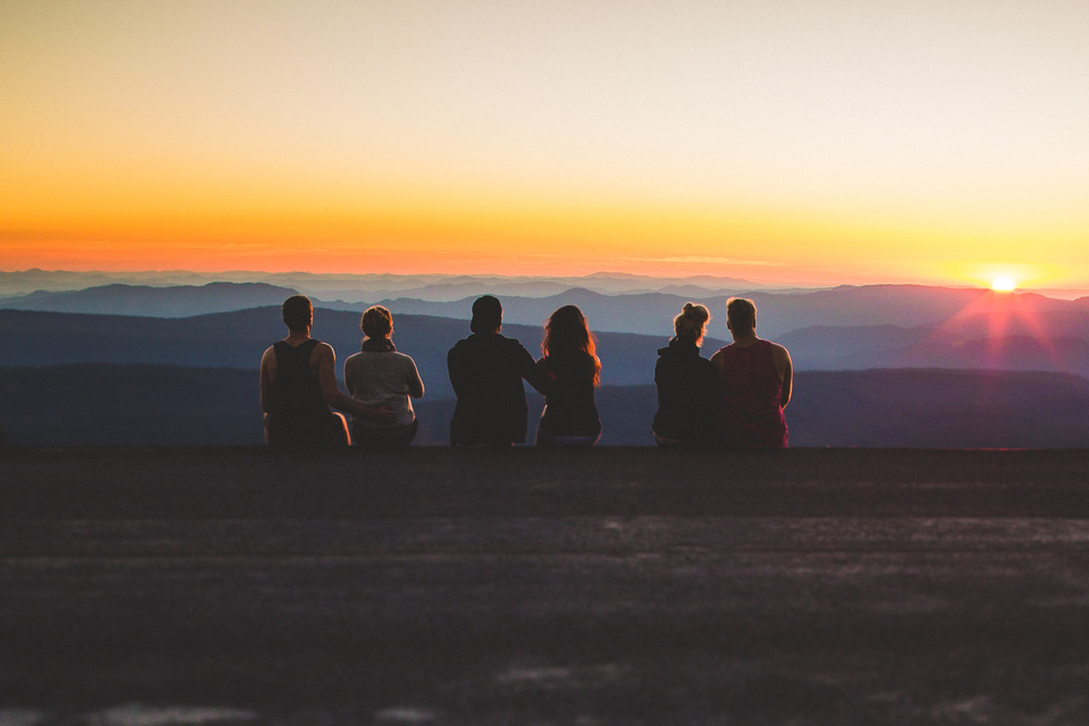 friends sitting facing sunset over mountains