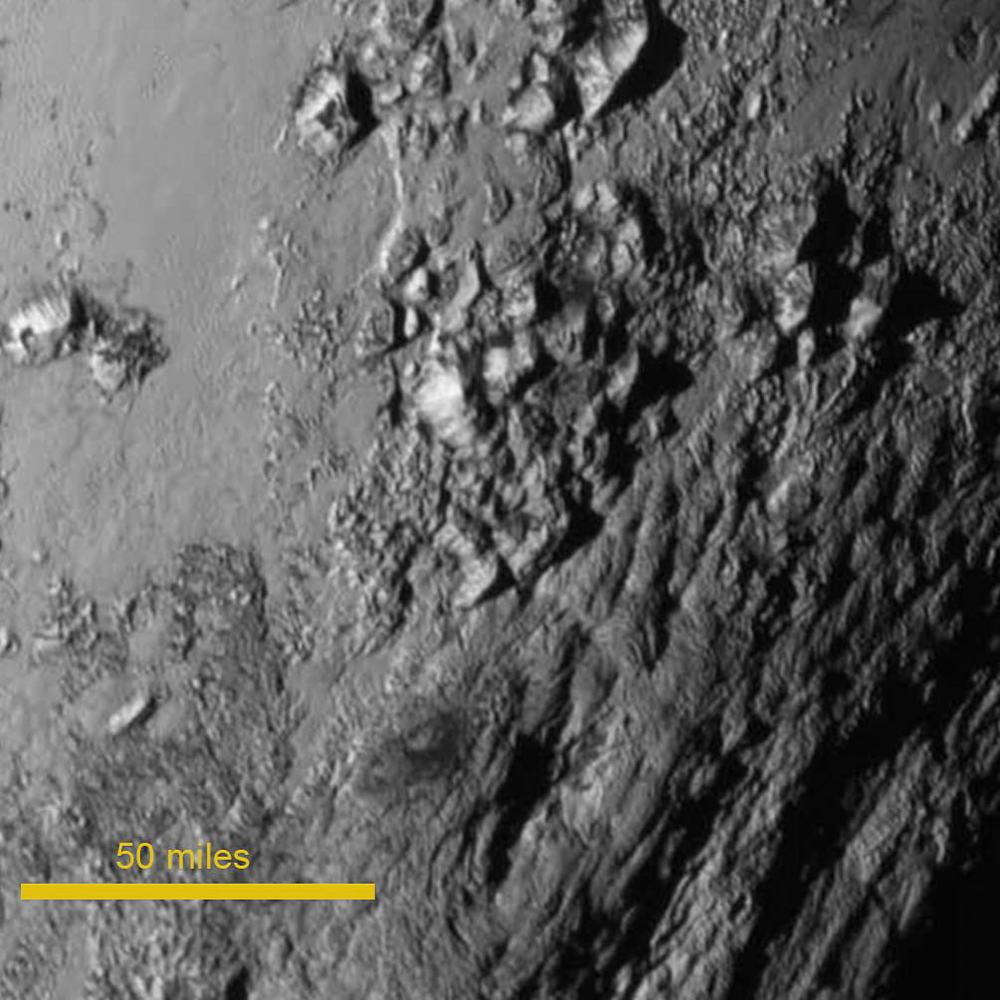 The very first close-up of #Pluto from @NASA #NewHorizons. Taken from around 500,000 miles from the surface, an hour and a half before closest approach. You can see features a mile across and mountains (made of ice) that are more than 2 miles high. Import