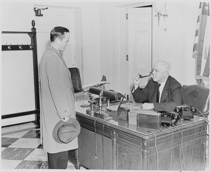 Photograph of William Simmons, receptionist at the White House, seated at his desk talking with an unidentified visitor.