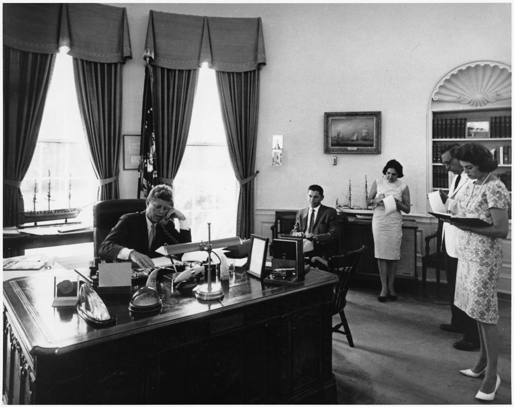 President Kennedy addresses AMVETS Convention in New York City by telephone.  President Kennedy, assistants. White House, Oval Office.