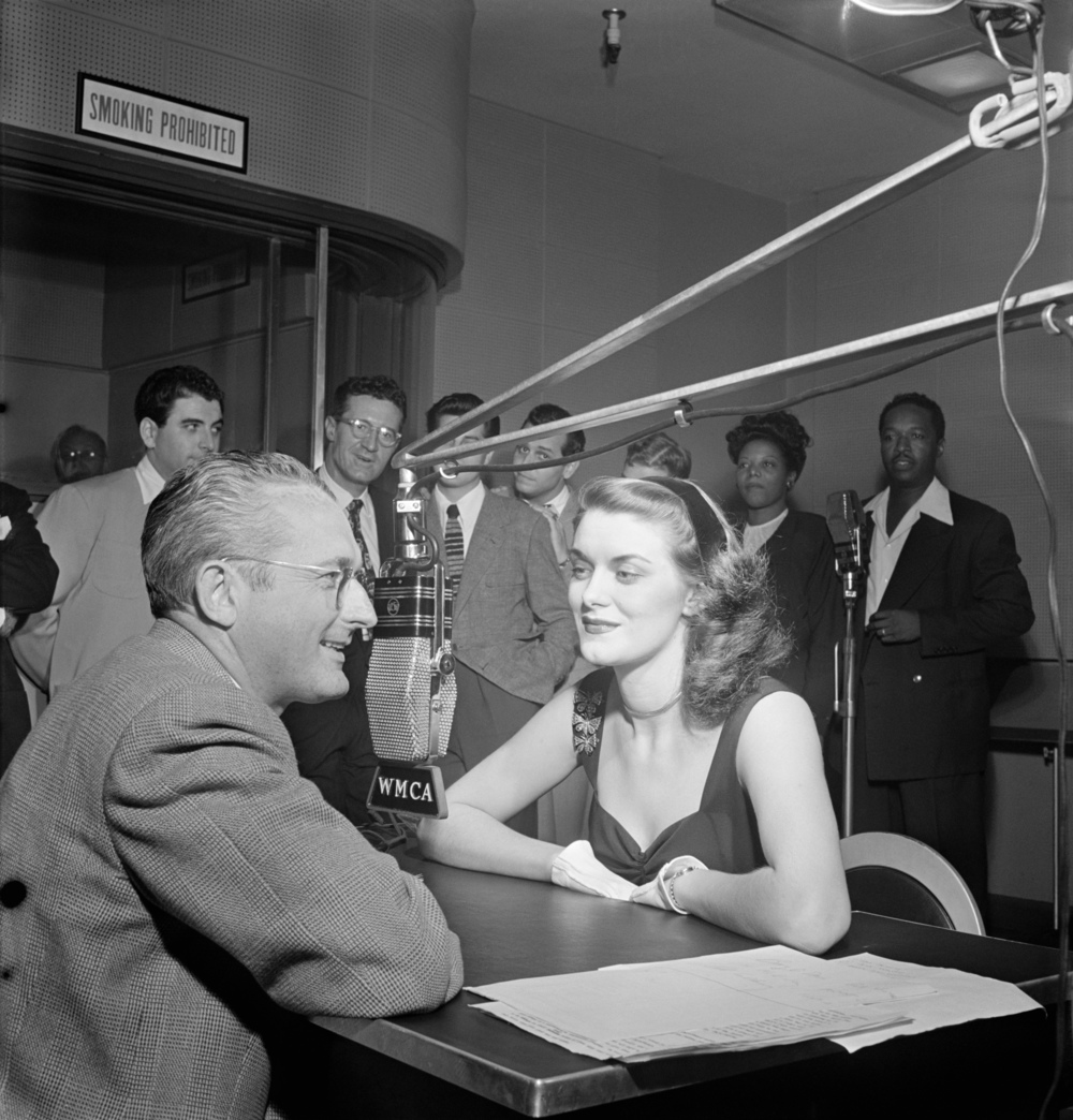 """Tommy Dorsey (left) interviews the English pigeon, Beryl Davis, for his first disc jockey stint, with such names as Georgie Auld, Ray McKinley, Mary Lou Williams, Josh White and others visible in the background """"Picture views of music world personalities,"""" Down Beat, v. 14, no. 21 (Oct. 8, 1947), p. 20."""