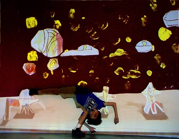 """Mini Big World"": Using drawings, cutouts, cardboard, and paper, kids created dioramas of imagined landscapes that were photographed and projected large-scale onto the wall. They then had a chance to be part of the worlds they created, and were photographed within their scenery. Pictured here is Hank on his alien planet."