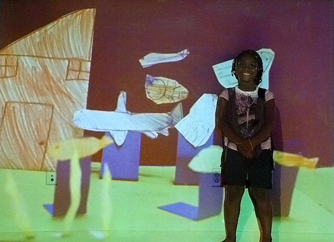 """Mini Big World"": Using drawings, cutouts, cardboard, and paper, kids created dioramas of imagined landscapes that were photographed and projected large-scale onto the wall. They then had a chance to be part of the worlds they created, and were photographed within their scenery. Pictured: Amariah and her undersea house."