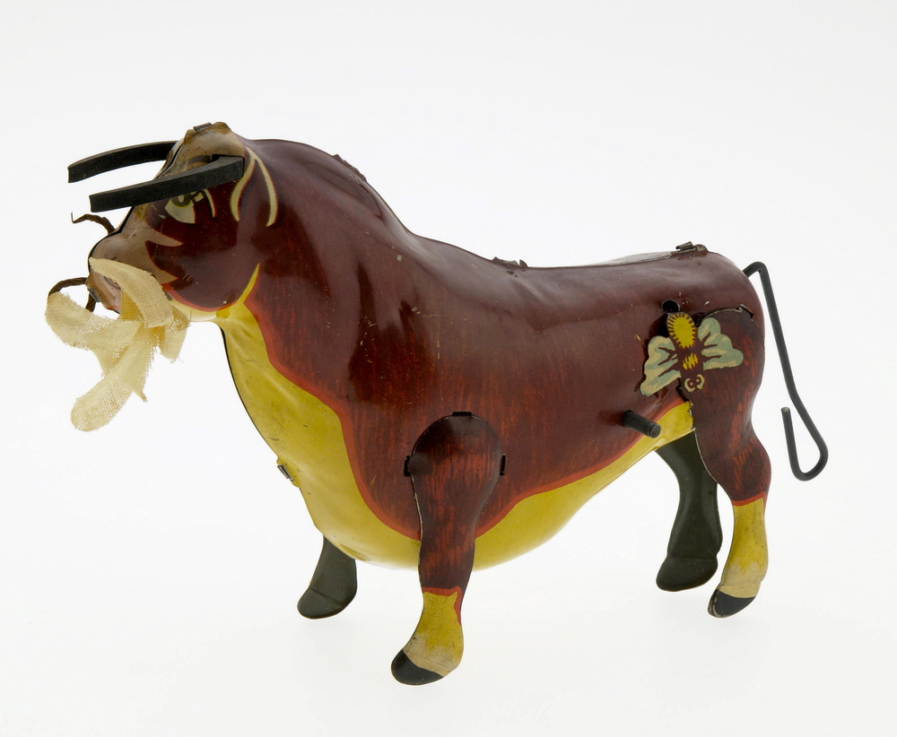 "Ferdinand the Bull Wind Up with Box (Louis Marx & Co., 1938). Nice image of Ferdinand, includes rubber horns and a flower in his mouth that are often missing. This is a very difficult to find toy with its original box. Toy measures 7"" x 3"", box measures 3.25"" x 5"" x 6"". Box and toy are both in Excellent to Near Mint. From the Larry Jacobs Collection."