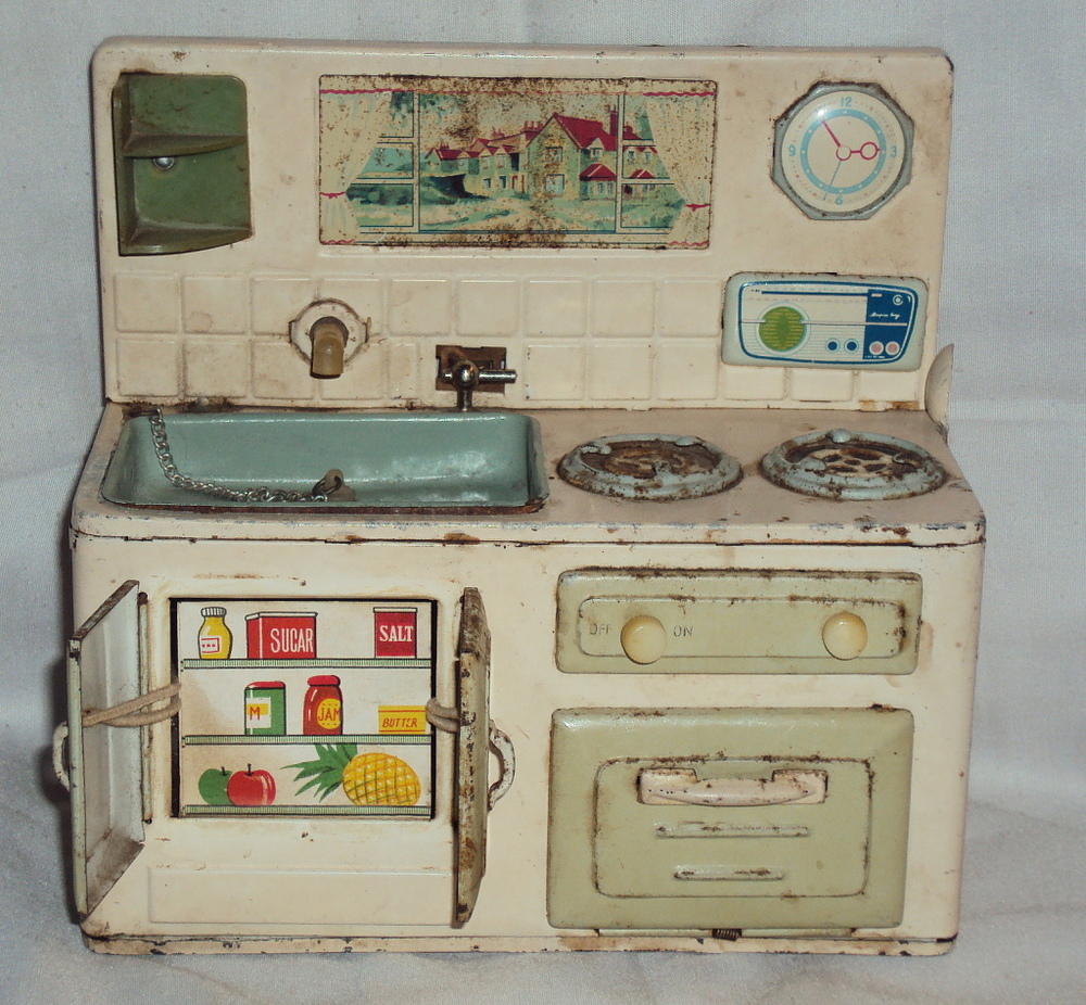 "Battery-operated tin kitchen. This one is a little beaten up, but when you turn the tap on, water flows and the gas burner ""fires"" up. via ebay"