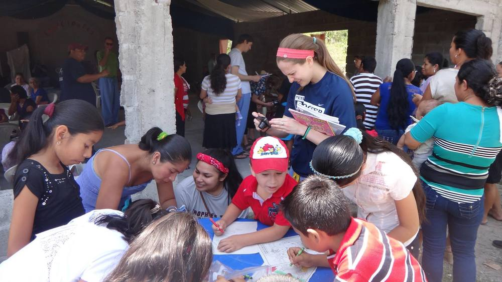 Brigade volunteers, Nicole Sanders (left in red bandana) and Barb McHugh (right with camera in hand), kept the children of this remote Honduran village occupied while their family members received medical care from the brigade's medical personnel.