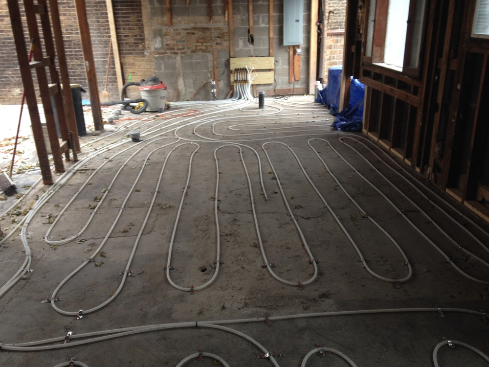 Heating tubes are laid on top of the existing slab awaiting the topping pour.  Tubes are evenly distributed to provide an even level of heat