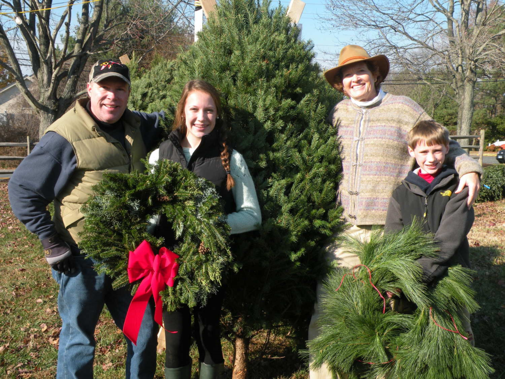 Left to Right:  Bill Allen, Talbot Optimist member, Katie Allen, youth volunteer, Susan Bohaker, Talbot Optimist member and Carson Allen, youth volunteer sell Christmas trees at the annual Talbot Optimist Christmas Tree sales in Easton on the grounds of the Easton YMCA.  Optimist will be selling trees throughout the holiday season.