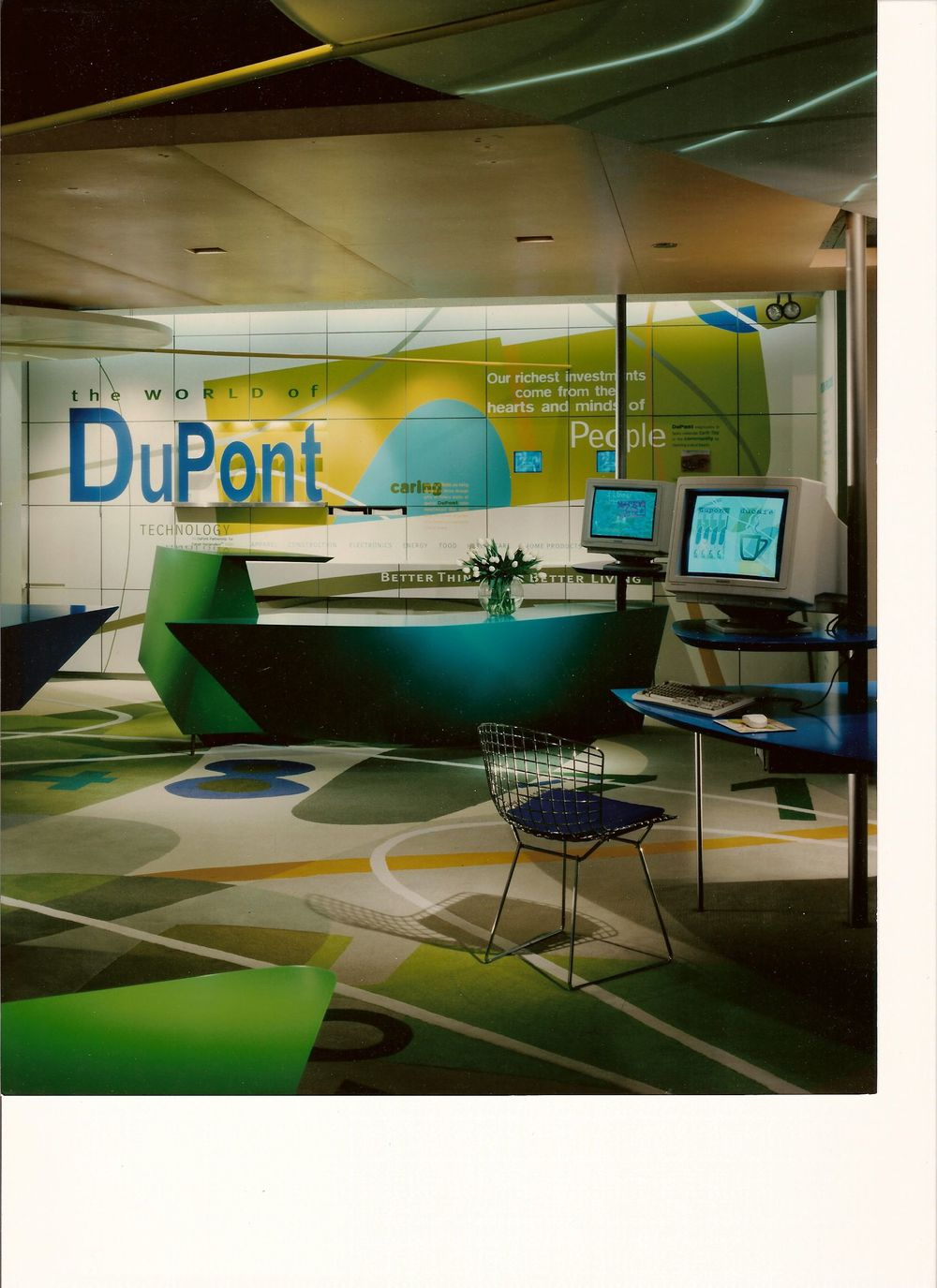 Corian wall panels, applied vinyl graphics, Corian clouds, neon work, custom millwork, and floor covering inlays by Ndio.