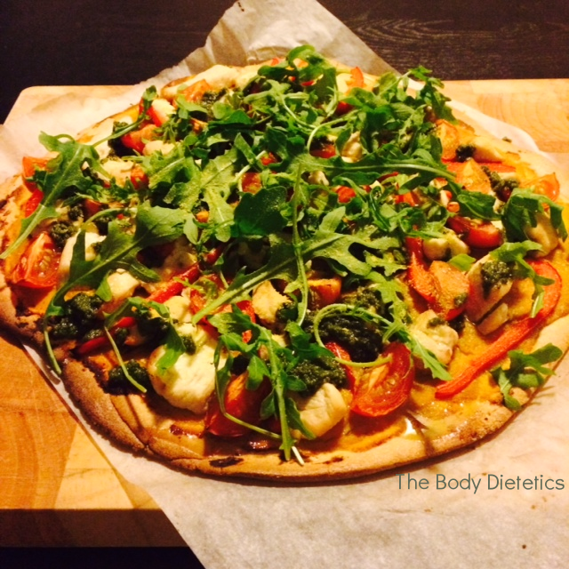 Paleo pizza with pesto chicken, tomato and rocket