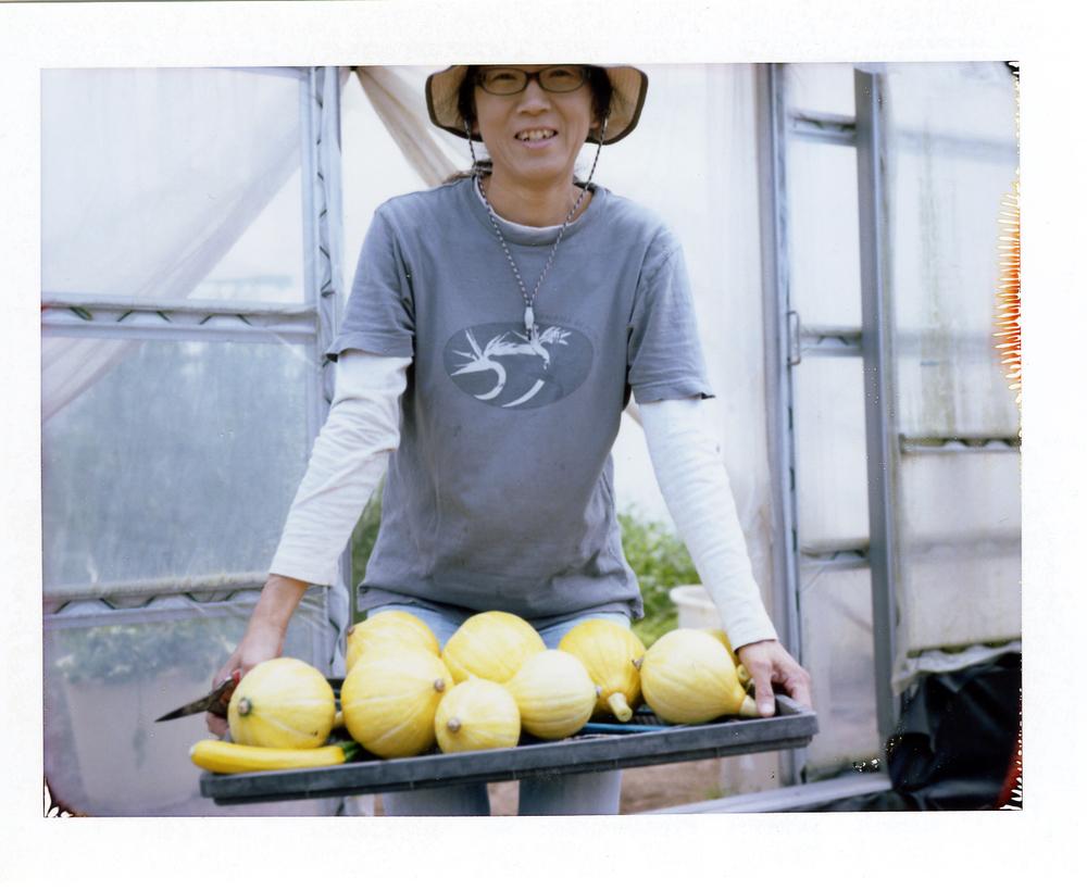 「ファーム・ベジコ」の長崎雅代さん。サラダで食べるととても美味しい自慢のコリンキーと。