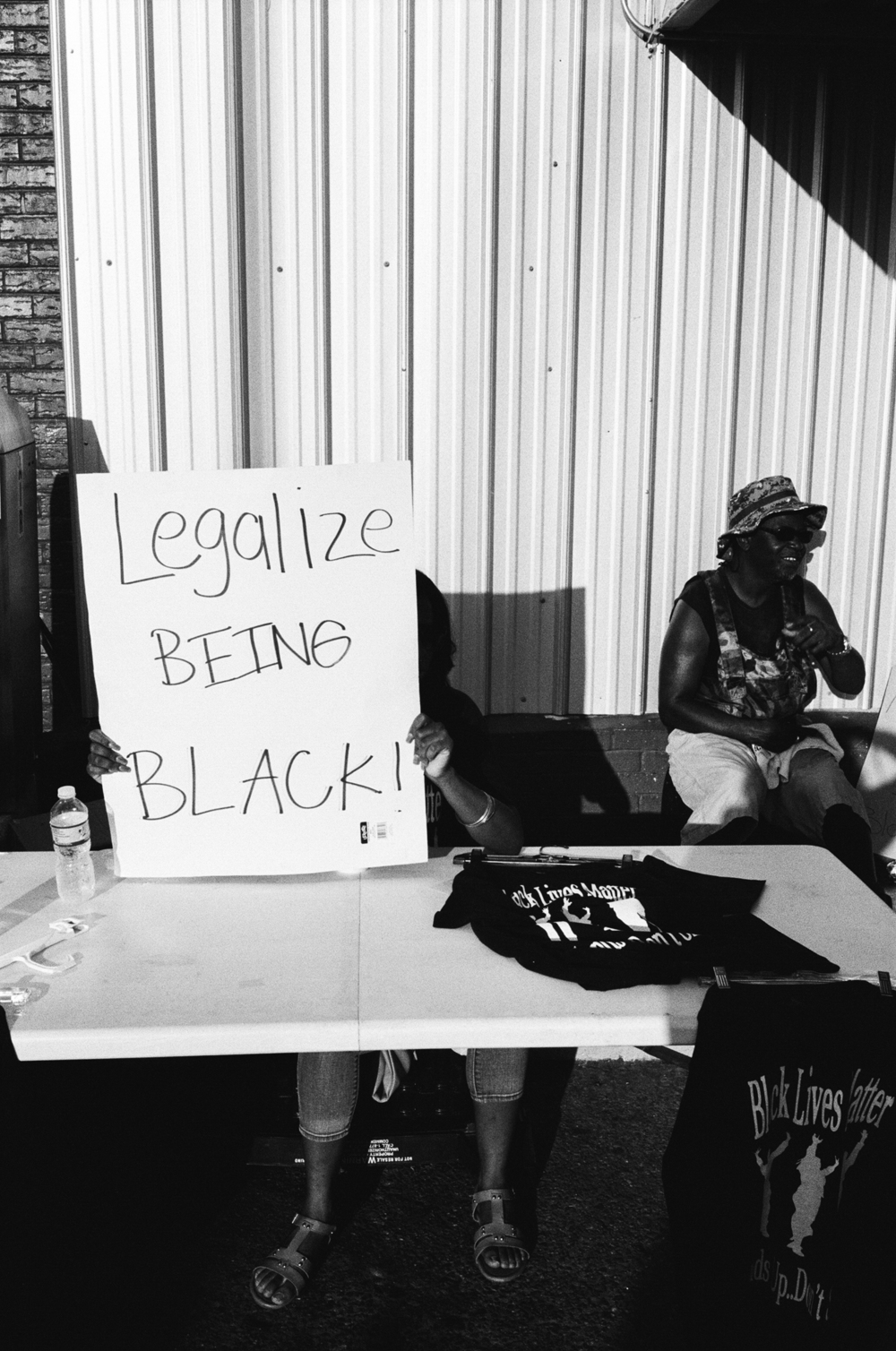 """Legalize being black!"" She hid behind the placard to avoid the sun, but her message remained."