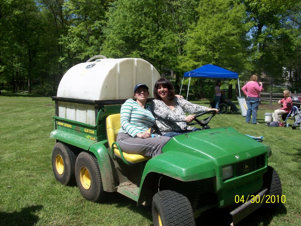 Salma and Carole driving a tractor on Arbor Day.