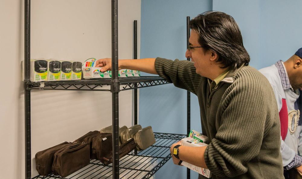 ACI Volunteer, José, stocks the food pantry.
