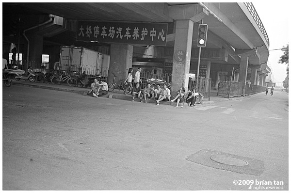 In front of the metro station, an elevated highway, and a bunch of people just chillin, I'm guessing they are street sellers taking a break.
