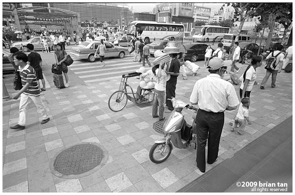 These are most likely unlicensed motorcycle taxis, found just about everywhere in China and especially at public transportation stations.