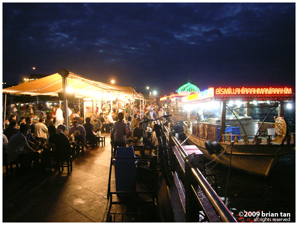 At night the fish sandwich shops come alive. The kitchen is on the rocking boat on the right, and the patrons on the left on terra firma.