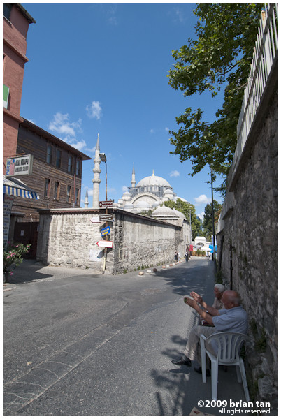 Two old residents sit in the shade sipping tea with Suleymaniye Mosque in the background