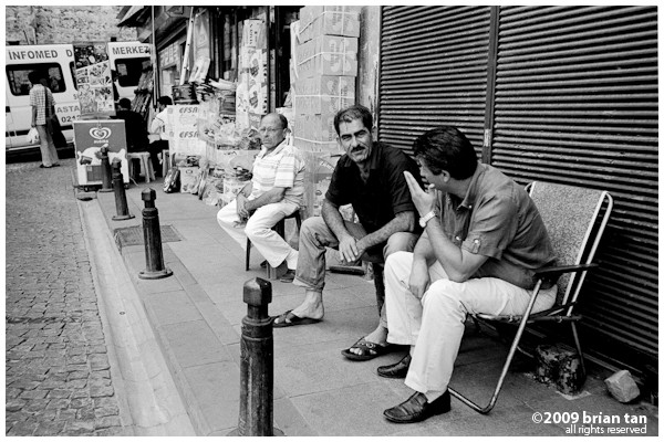 Just about anywhere in Istanbul, you get people sitting on the sidewalks just chatting away. Somewhere in the picture they should have a small cup of tea.