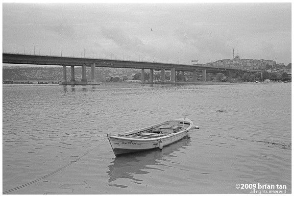 Lone boat, Halic (Golden Horn) Bridge in the background. In Balat.
