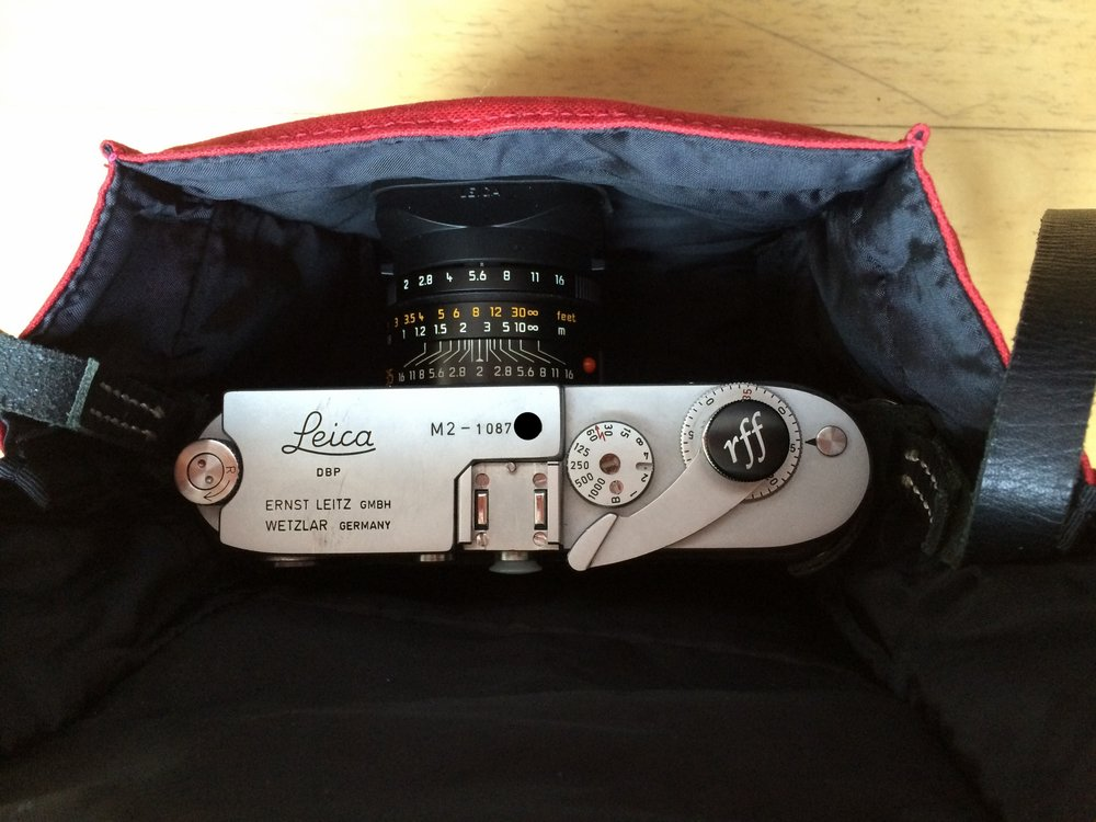 "ACAM-75 with a Leica M2 and 35mm Summicron ASPH. To be fair, it also has a Abrahamsson Rapidwinder attached to it and a half case. The elastic band closes ok but it is definitely pushing the boundary of ""fit""."