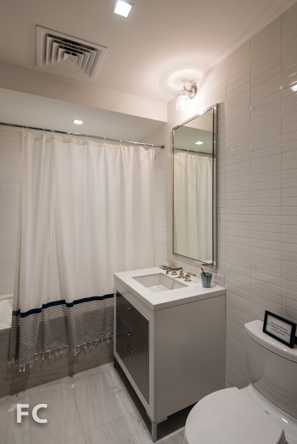 Secondary bathroom with custom white lacquer vanity including water resistant galvanized drawer fronts.
