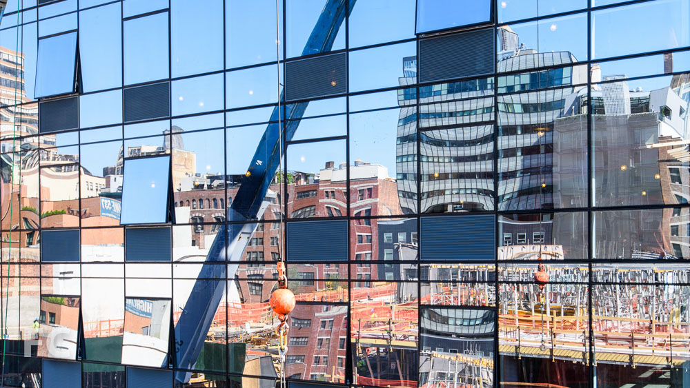 Reflection of the site on the newly installed facade of 507 W 28.
