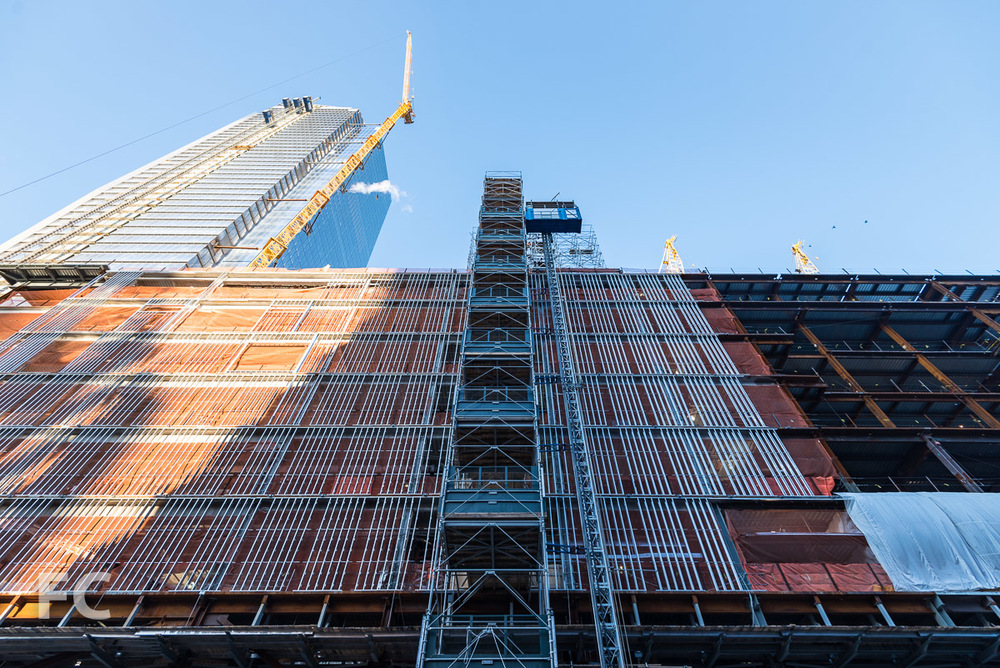 Looking up at the east facade of the retail building with 10 Hudson Yards rising above (left).