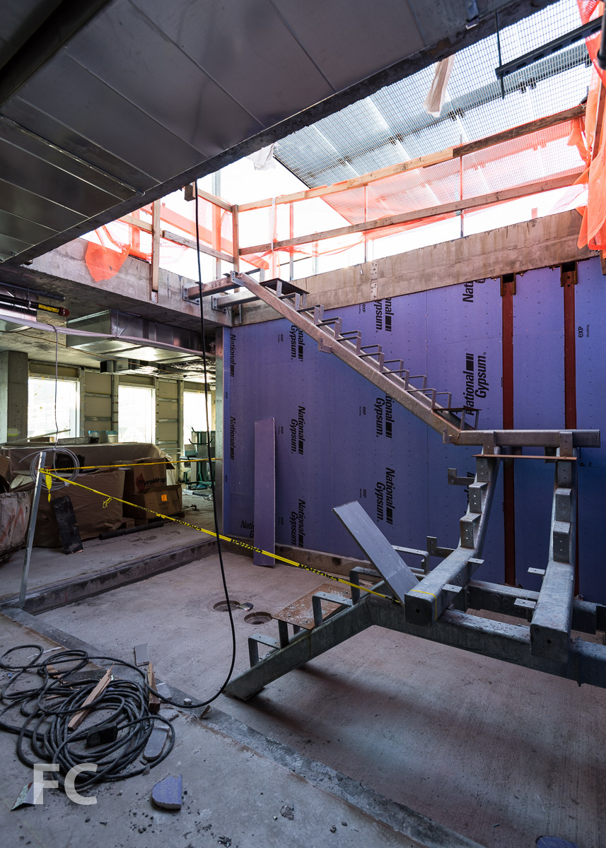 Stair under construction inside a penthouse unit's sunken courtyard.