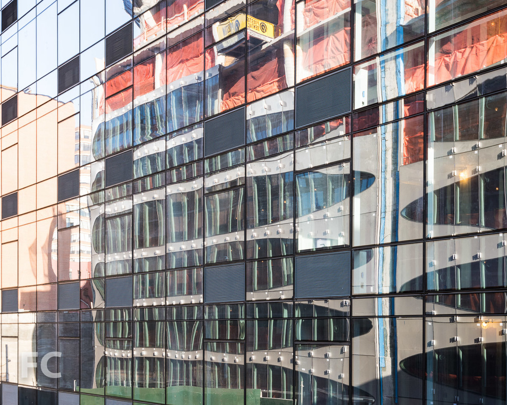 Reflection of the façade in the curtain wall of 323 Tenth Avenue.