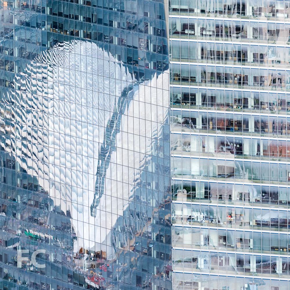 World Trade Center Transportation Hub reflected in the facade of 1 World Trade Center.