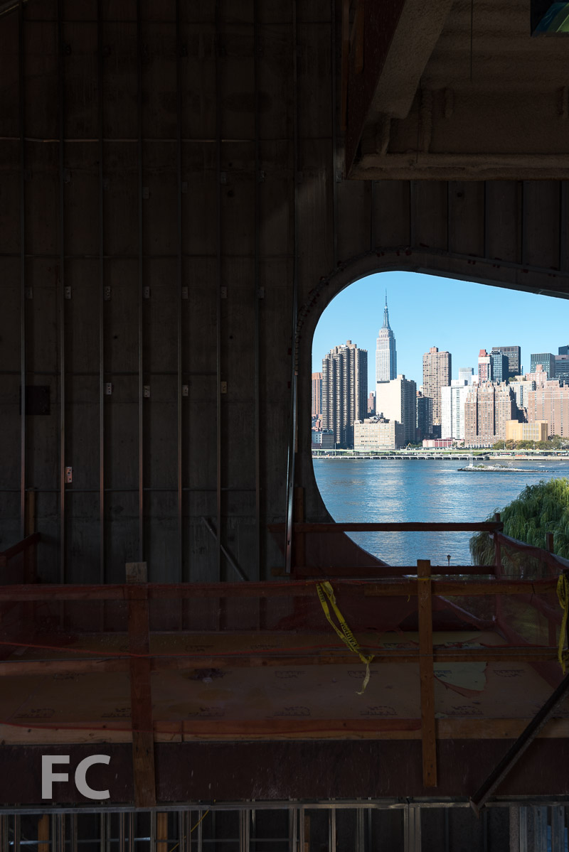 An organic-shaped opening frames the Manhattan skyline.