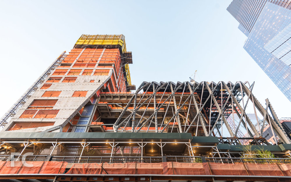 Looking up at the south facade of 15 Hudson Yards (left) and the Shed (center).