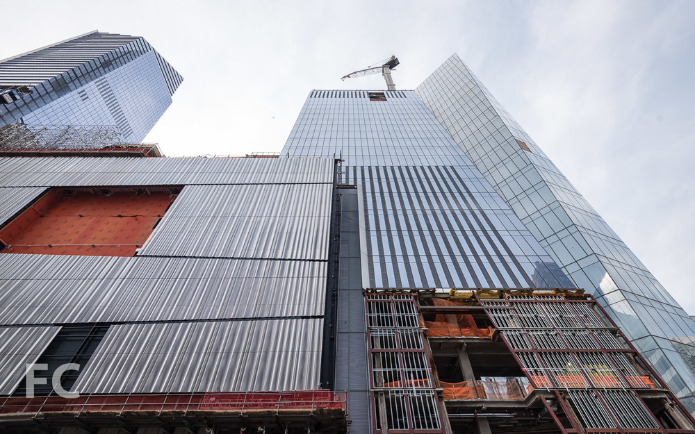 Looking up at the east facade of the retail podium (left) and 30 Hudson Yards (right).