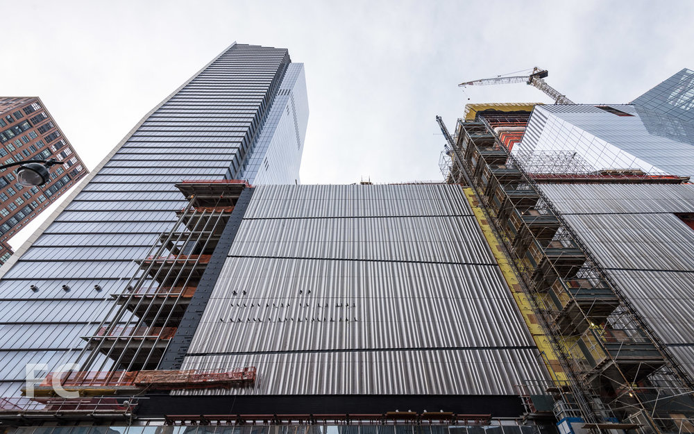 Looking up at the east facade of 10 Hudson Yards (left) and the retail podium (center).