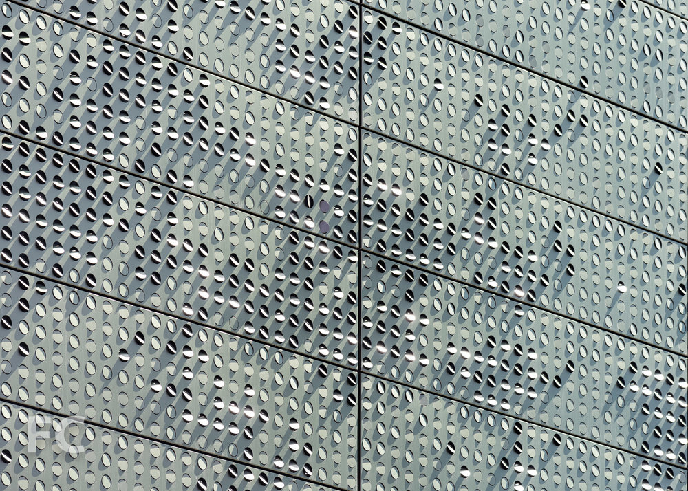 Close-up of the perforated metal panel façade of The Bloomberg Center.