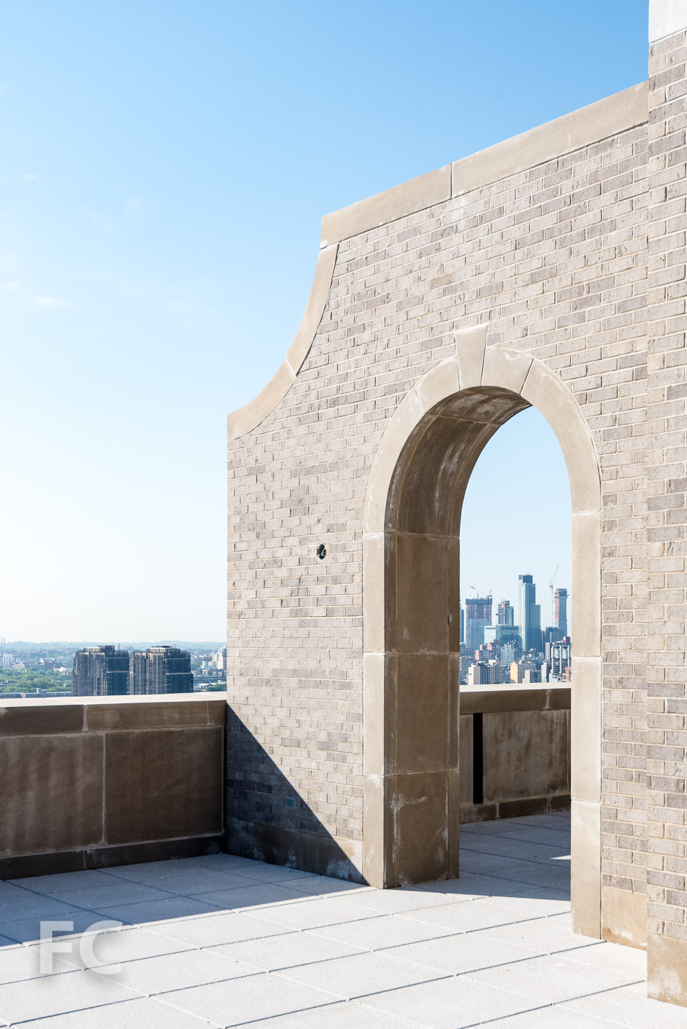 Long Island City framed by an arched opening on the rooftop terrace.