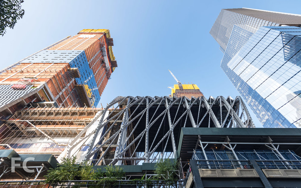 Looking up at the south façade of The Shed (center) and 15 Hudson Yards (left).
